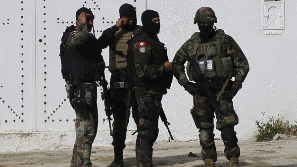 Tunisian counter-terrorism police stand guard near a house in Raoued
